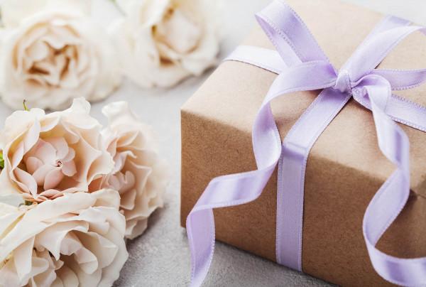 geschenkpacket mit zart lila schlaufe neben weissen rosen